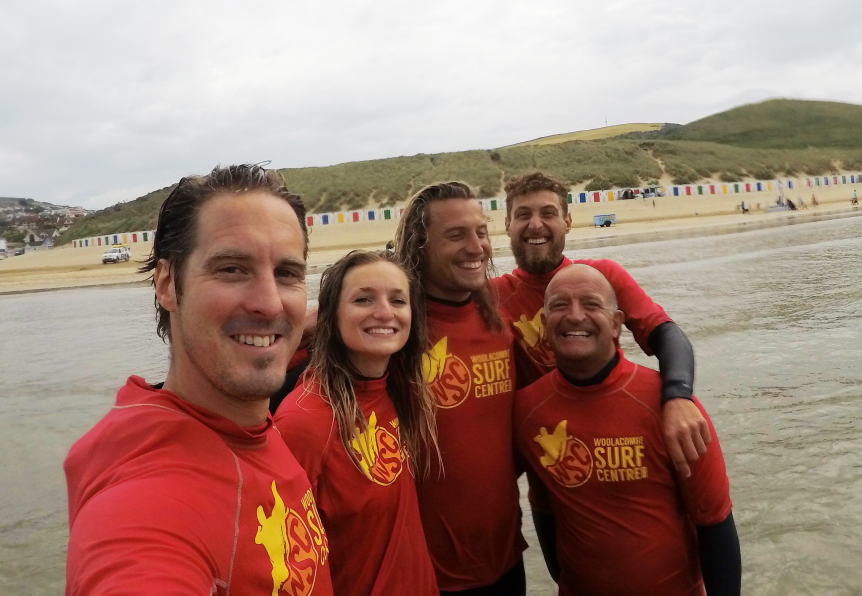 Woolacombe Surf Centre team photo on a group surf lesson on Woolacombe beach