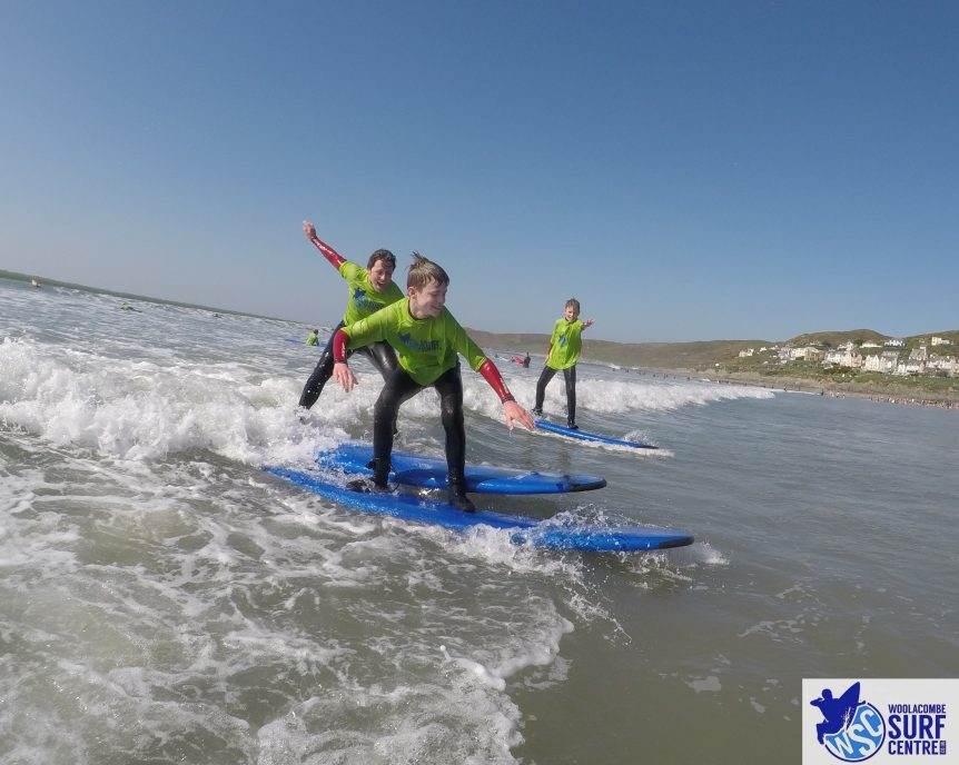 Family surfing the same wave, learning to surf in the school holidays, family fun activity with Woolacombe Surf Centre