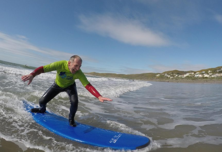 first time surfer enjoying the ride and getting free photos of his experience with Woolacombe Surf Centre