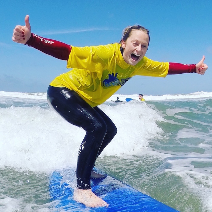 Happy smiley surfer learning to surf in the sunshine in the summer on Woolacombe Beach with Woolacombe Surf Centre